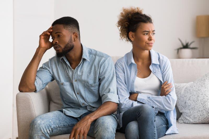 Pares pretos virados que evitam o contato de olho que senta-se no sofá imagem de stock