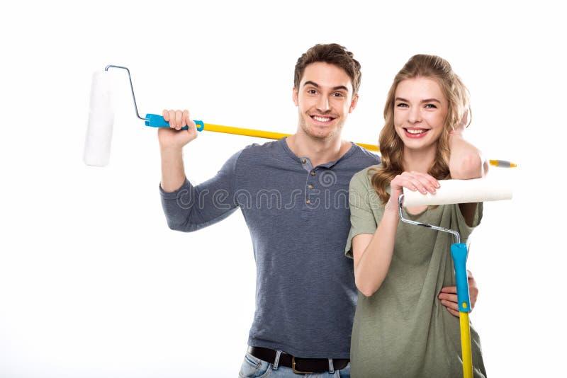 Pares profesionales jovenes que sostienen los rodillos de pintura aislados en blanco fotografía de archivo libre de regalías