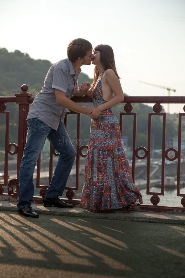 Pares que abraçam e que beijam em uma ponte imagens de stock royalty free