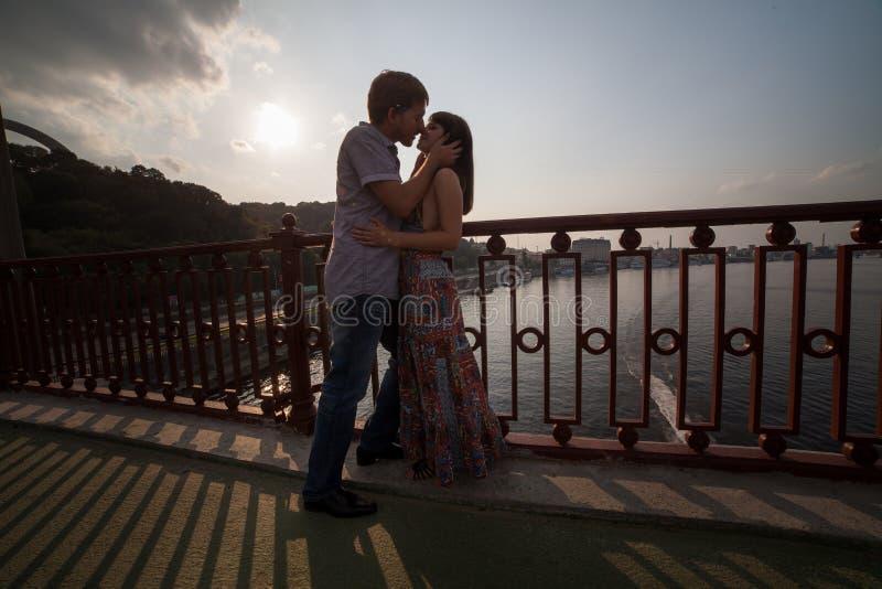 Pares que abraçam e que beijam em uma ponte imagem de stock