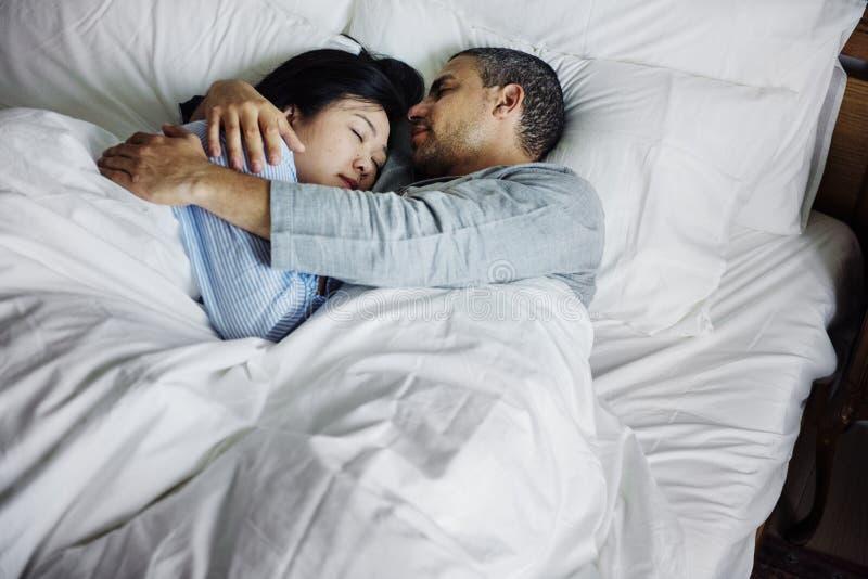 Pares que abraçam em uma cama fotografia de stock