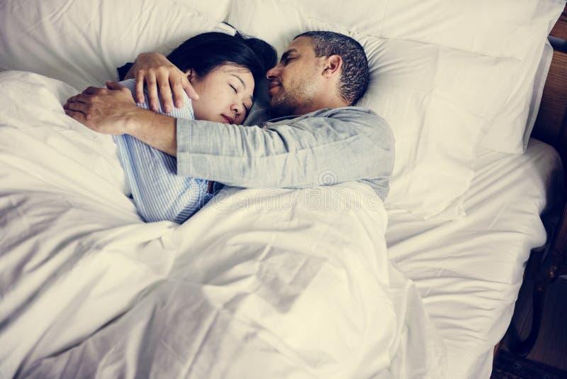 Pares que abraçam em uma cama imagens de stock