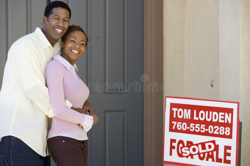 Pares que abraçam fora de sua casa nova fotos de stock royalty free