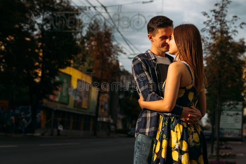 Pares que abraçam na rua o homem estica para um beijo à fêmea, menina Menina no vestido imagem de stock royalty free