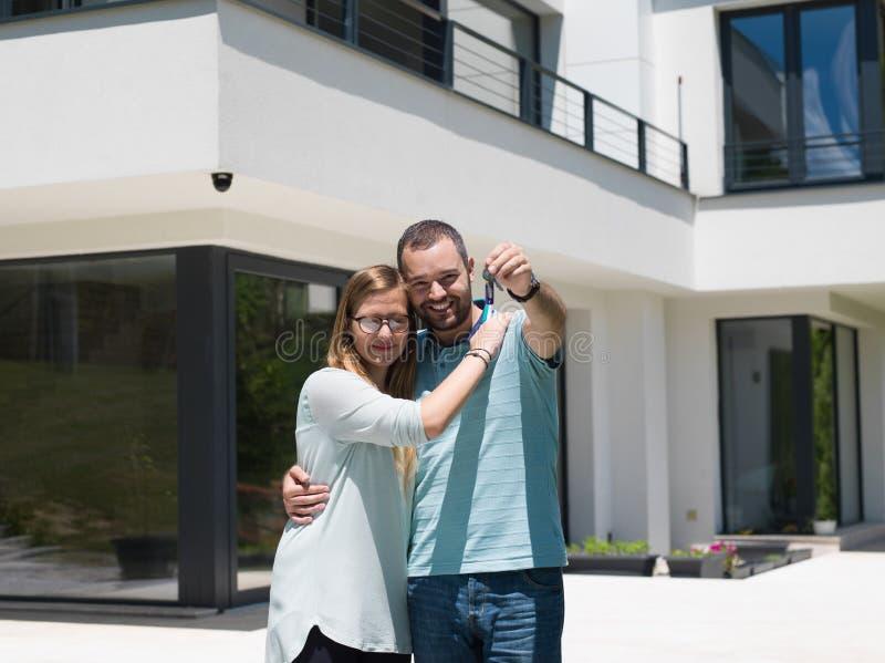 Pares que abrazan delante de nuevo hogar de lujo imagen de archivo libre de regalías