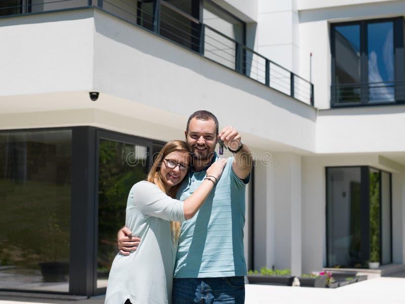 Pares que abrazan delante de nuevo hogar de lujo fotografía de archivo