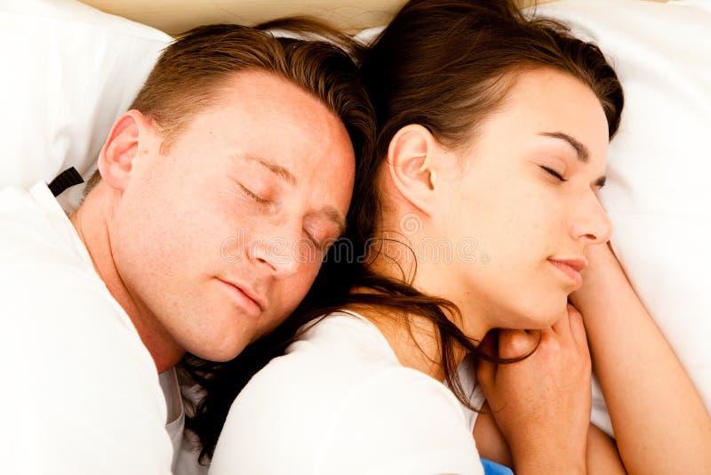 Pares que abrazan en cama imagen de archivo