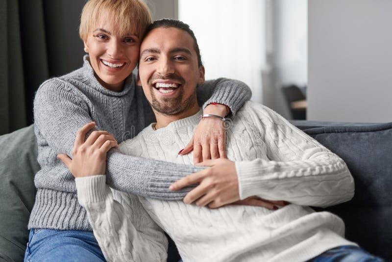 Pares que abrazan en el sofá durante fecha fotografía de archivo libre de regalías