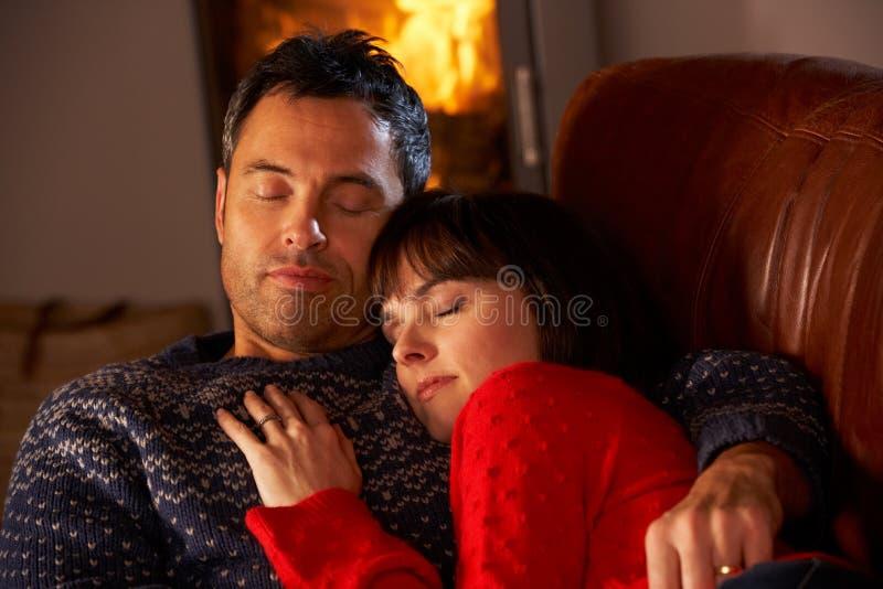 Pares que abrazan en el sofá por el fuego de registro acogedor imagen de archivo libre de regalías