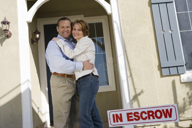 Pares que abrazan en Front Of New House foto de archivo