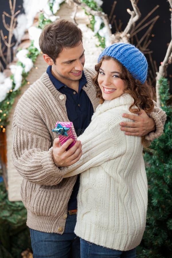 Pares que abrazan en tienda de la Navidad foto de archivo libre de regalías