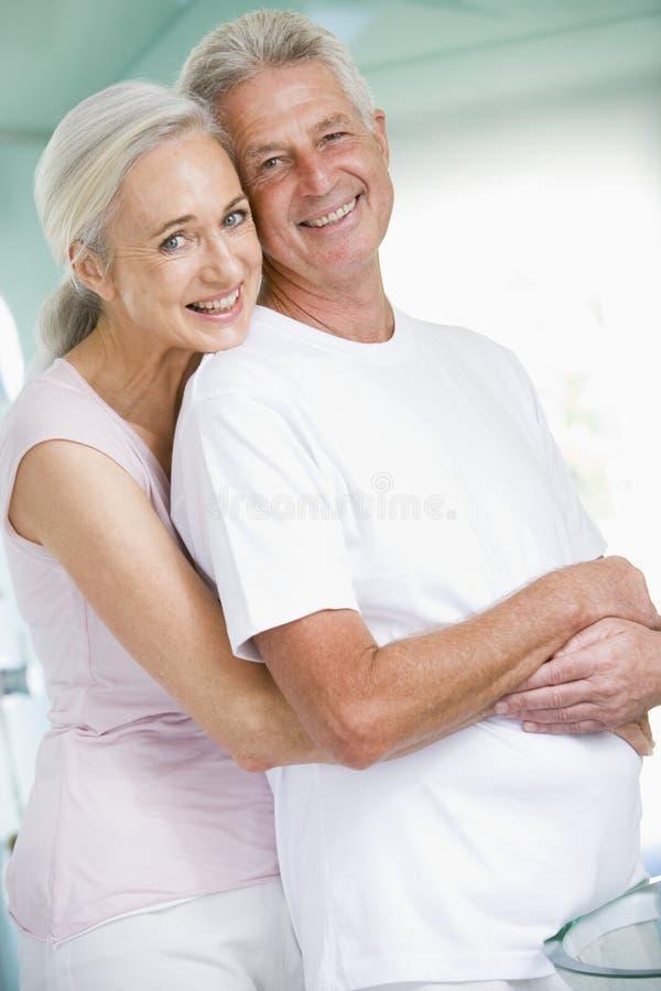 Pares que abrazan en un balneario y una sonrisa foto de archivo libre de regalías