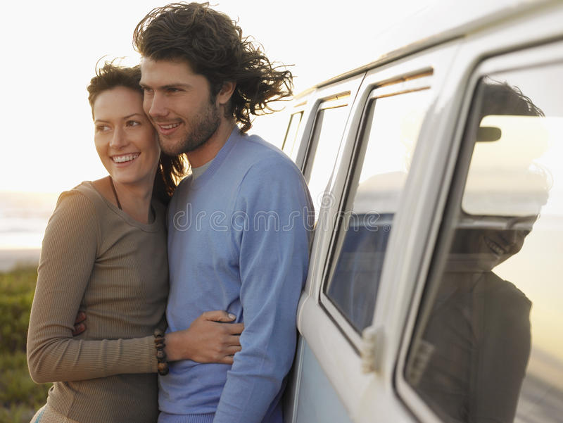 Pares que abrazan por Campervan en la playa fotos de archivo libres de regalías