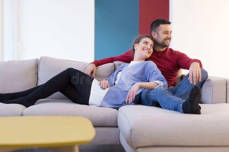 Pares que abrazan y que se relajan en el sofá foto de archivo