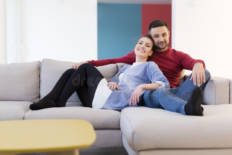 Pares que abrazan y que se relajan en el sofá imagen de archivo