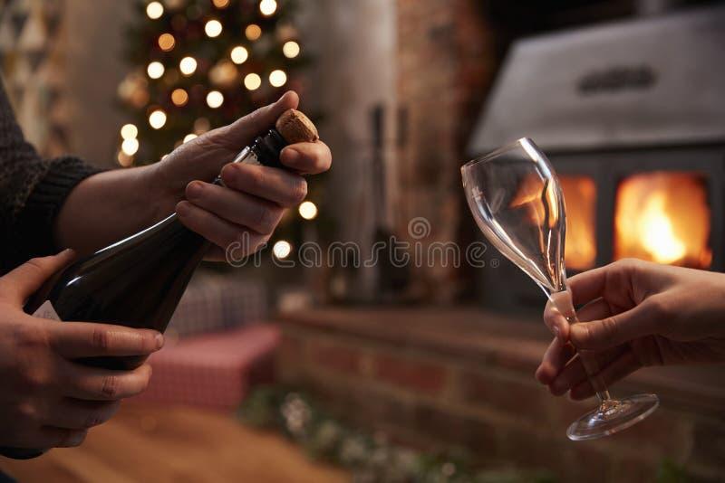 Pares que abrem o Natal de Champagne In Room Decorated For foto de stock