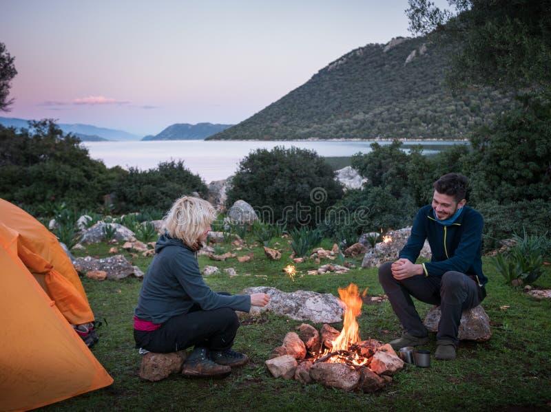 pares que acampam com fogueira imagem de stock royalty free