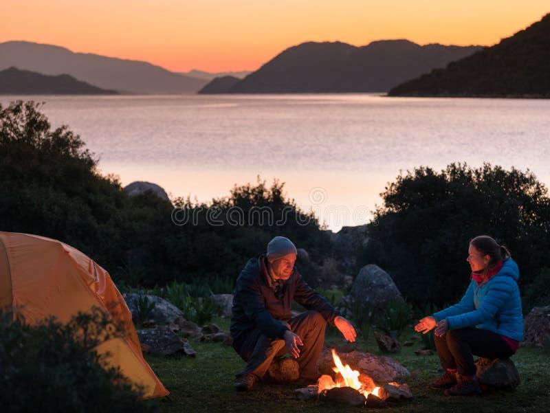 Pares que acampam com fogueira e barraca fotografia de stock royalty free