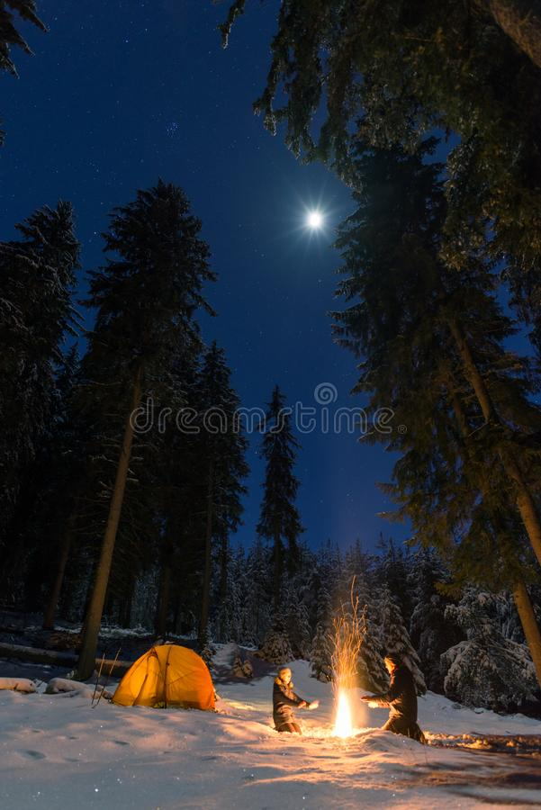 Pares que acampam com fogueira e barraca fora foto de stock royalty free