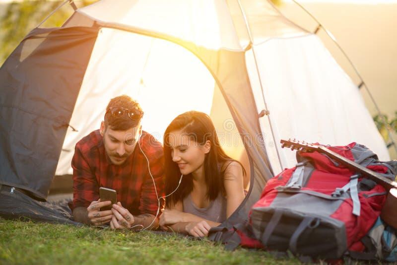 Pares que acampan en la tienda que toma el selfie usando smartphone foto de archivo libre de regalías