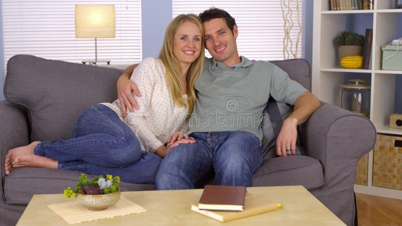 Pares que afagam no sofá fotos de stock