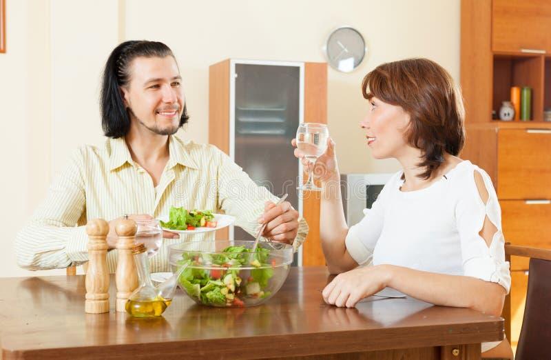 Pares que almuerzan con las verduras en hogar imagen de archivo