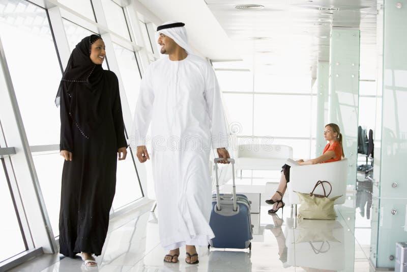 Pares que andam através da sala de estar da partida do aeroporto fotografia de stock royalty free