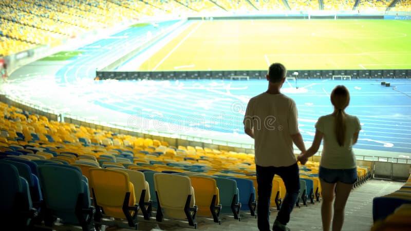 Pares que andam em torno do estádio vazio após o fósforo de futebol, momentos entusiasmados, data fotografia de stock