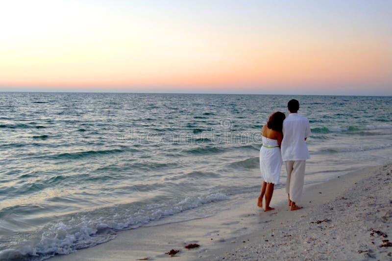 Pares que andam na praia no por do sol imagem de stock