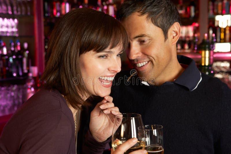 Pares que apreciam a bebida junto na barra fotografia de stock royalty free