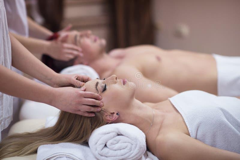 Pares que apreciam a massagem principal nos termas foto de stock royalty free