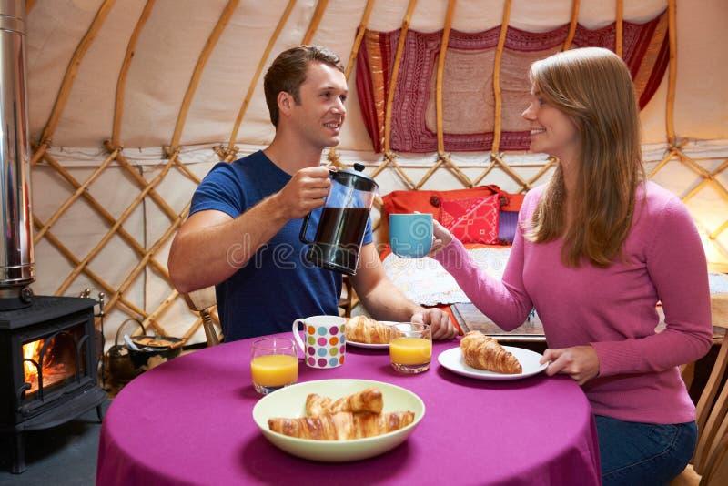 Pares que apreciam o café da manhã enquanto acampando em Yurt tradicional imagens de stock