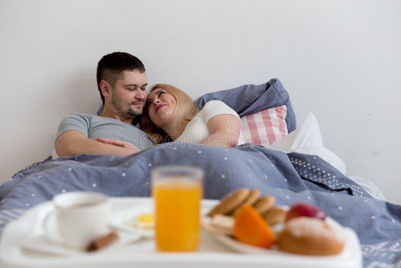 Pares que apreciam o café da manhã na cama fotografia de stock