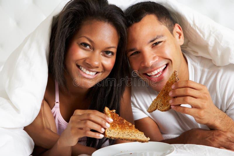 Pares que apreciam o café da manhã na cama imagem de stock