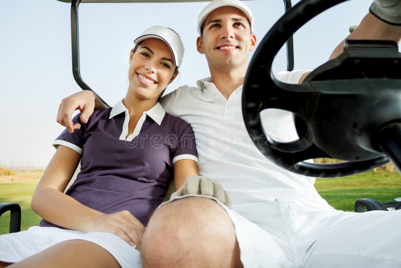 Pares que apreciam um jogo do golfe imagens de stock