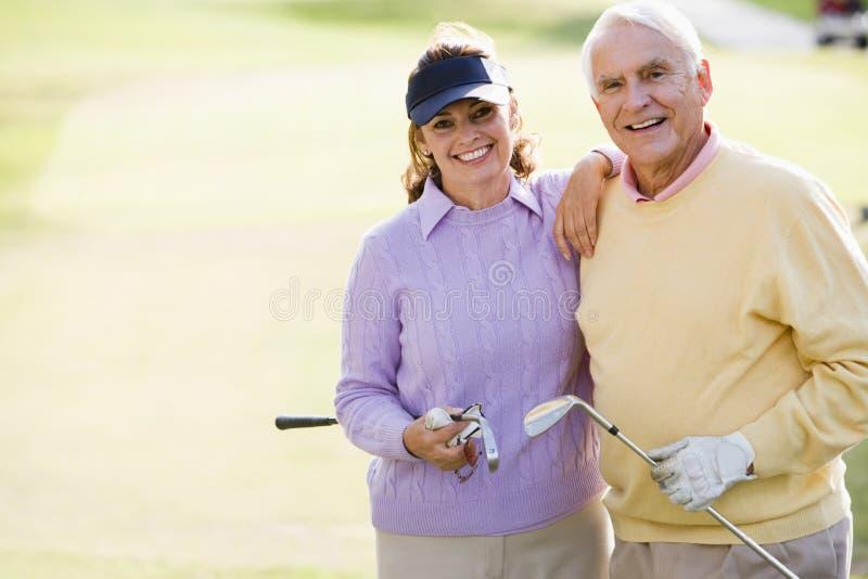 Pares que apreciam um jogo do golfe fotografia de stock royalty free
