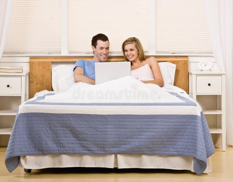 Pares que apreciam usando o portátil na cama imagens de stock royalty free