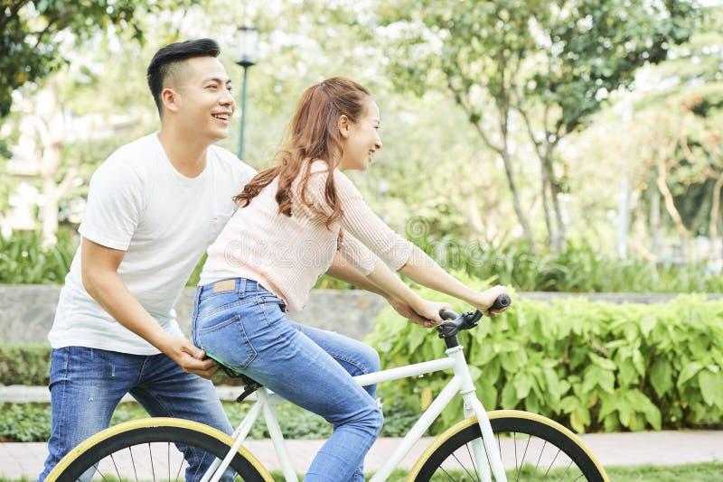 Pares que aprenden montar en la bicicleta fotografía de archivo libre de regalías