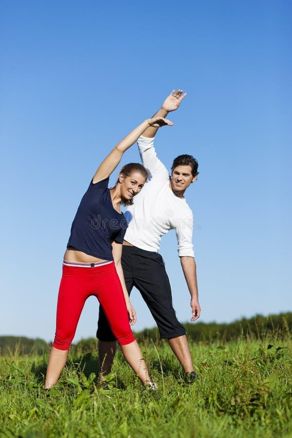 Pares que aquecem para o exercício no verão fotografia de stock royalty free