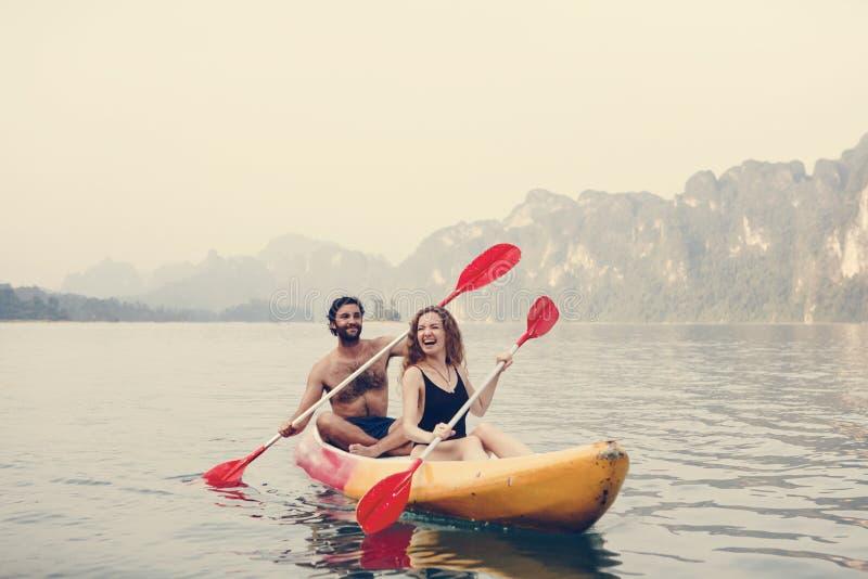 Pares que baten la canoa en el lago imagen de archivo libre de regalías