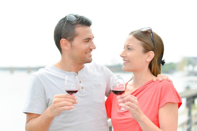 Pares que bebem fora o vinho tinto do vidro foto de stock
