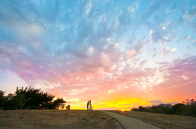 Pares que beijam durante um por do sol colorido imagem de stock