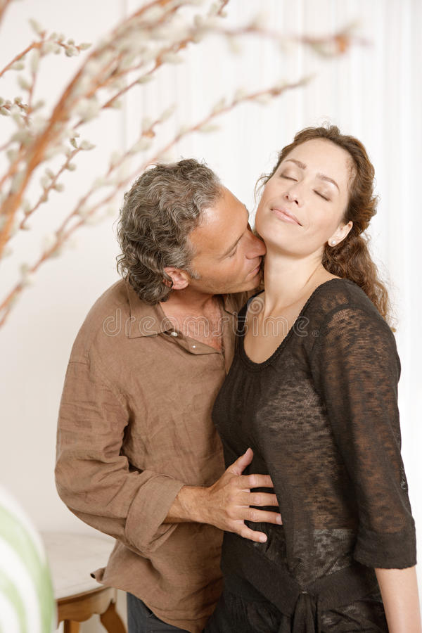 Pares que beijam em casa. imagem de stock royalty free