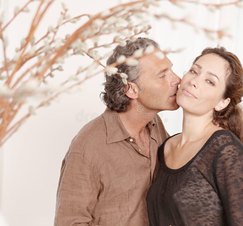 Pares que beijam em casa. imagens de stock