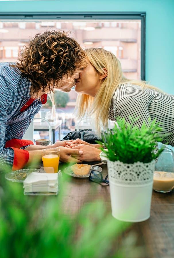 Pares que beijam em um café foto de stock