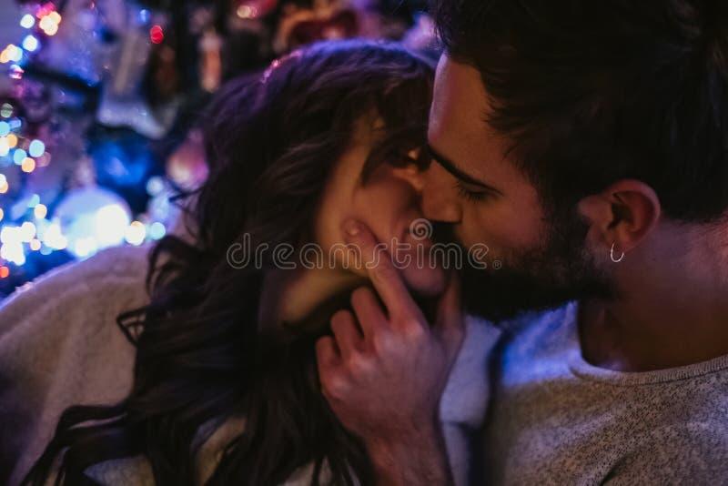Pares que beijam na frente da árvore de Natal fotografia de stock royalty free