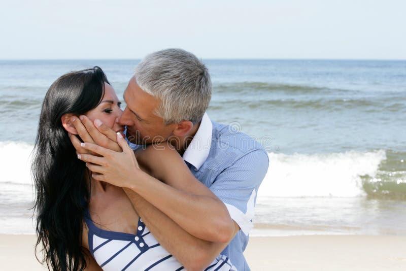 Pares que beijam na praia fotografia de stock royalty free