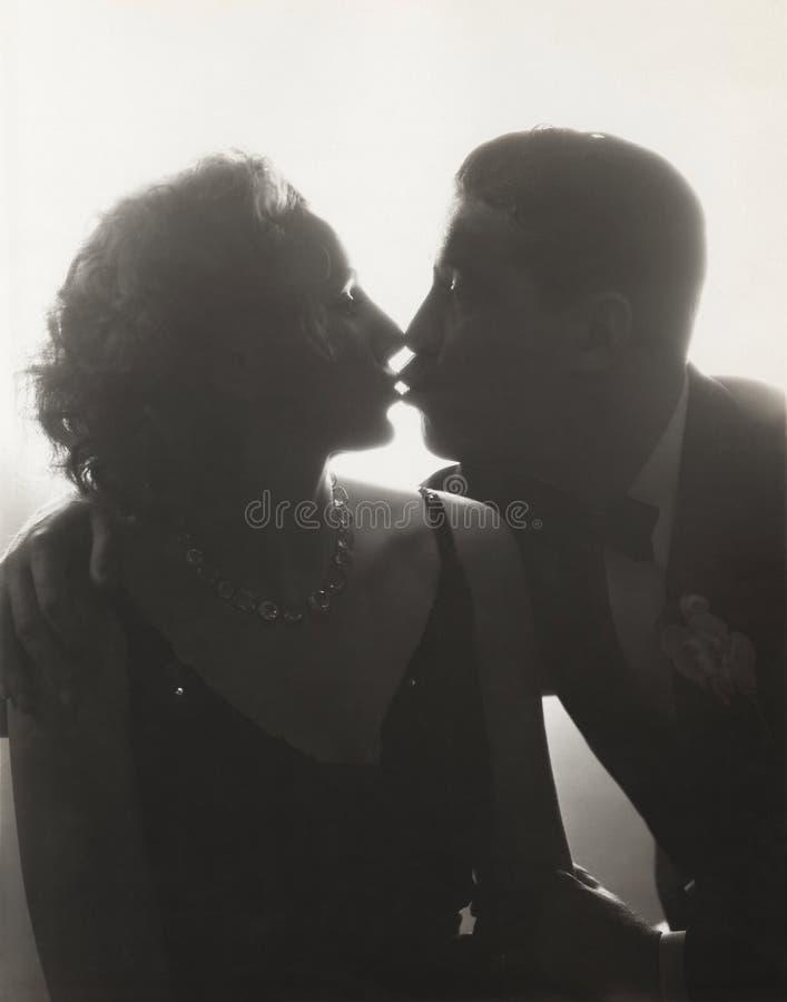 Pares que beijam na silhueta fotografia de stock