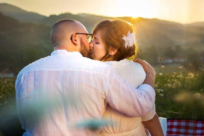 Pares que beijam no piquenique com opinião do por do sol imagens de stock royalty free