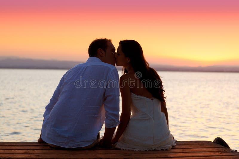 Pares que beijam no por do sol que senta-se no molhe fotografia de stock